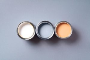 three paint cans sitting next to each other. one is cream, one is gray, and one is peach